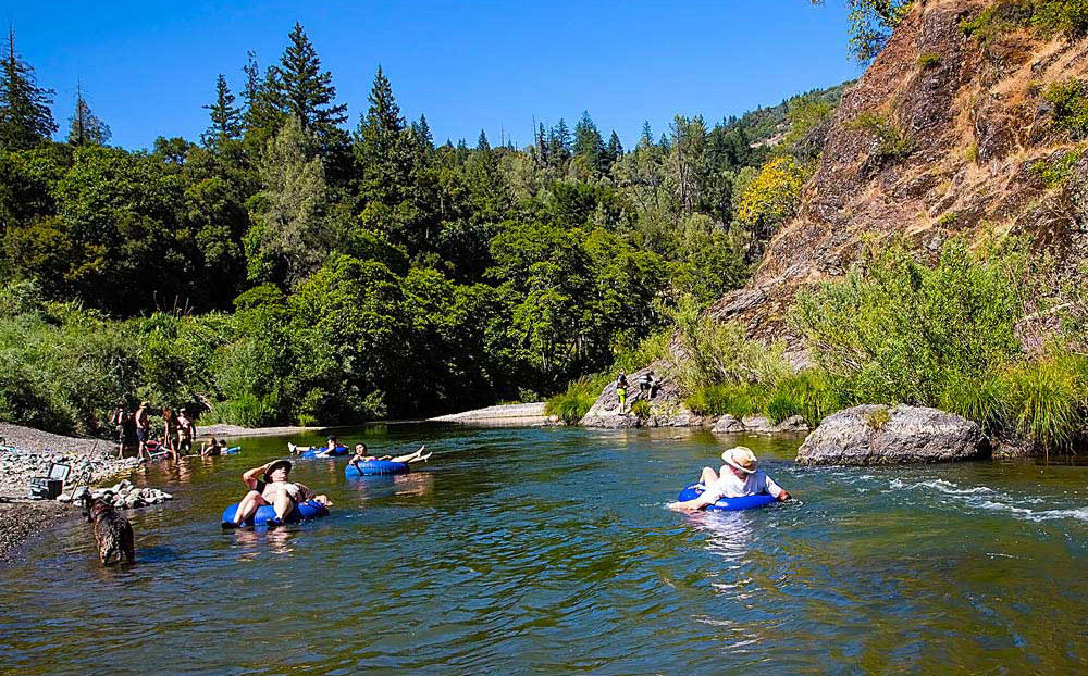 Leisure seekers float on a river on inner tubes.