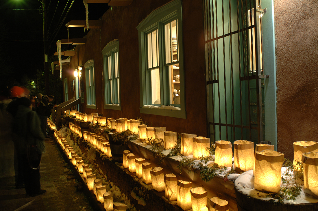 Luminarias lined up against a wall overlooked by windows.
