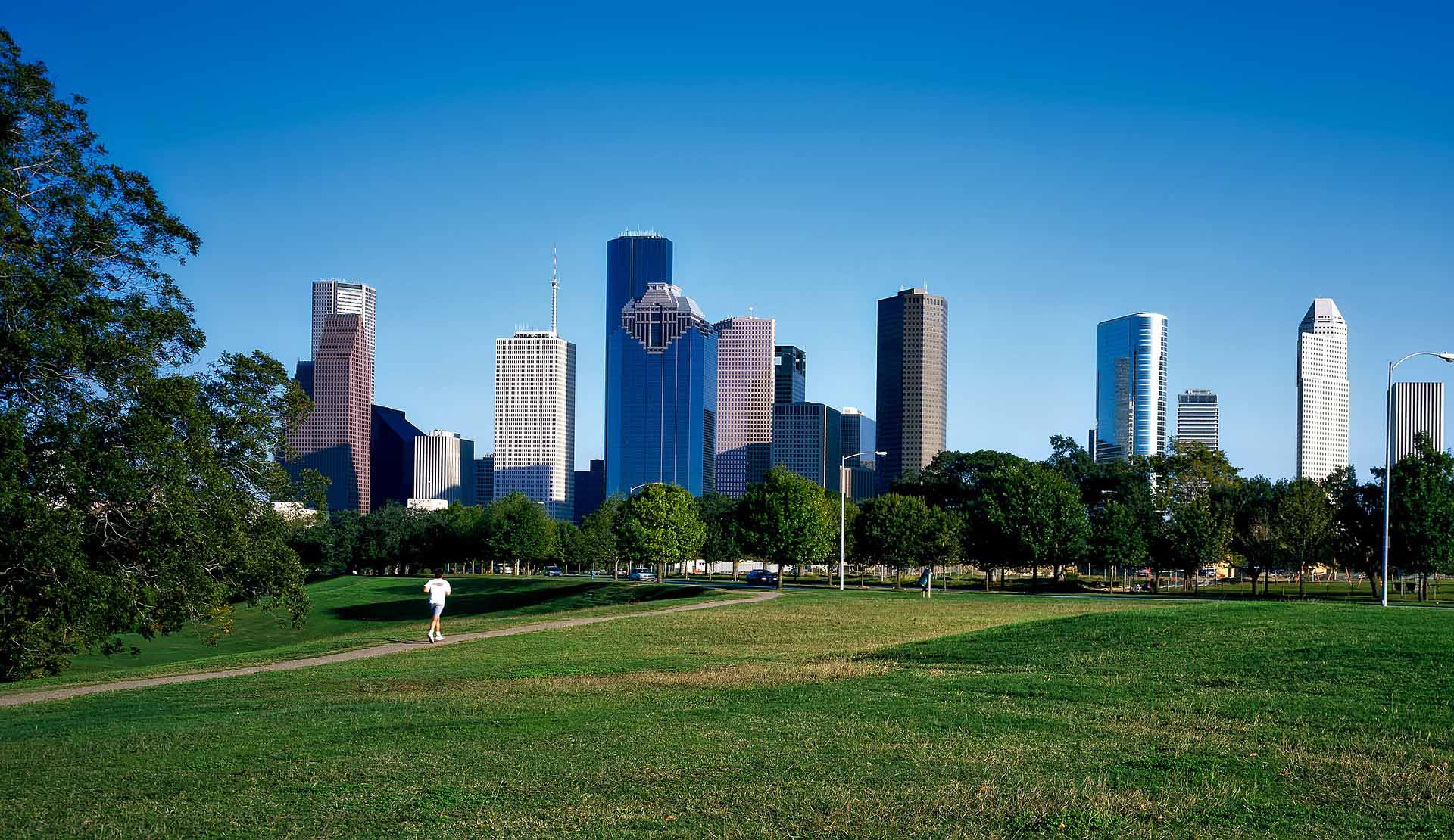 A park in foreground, gleaming Houston skyline in distance.