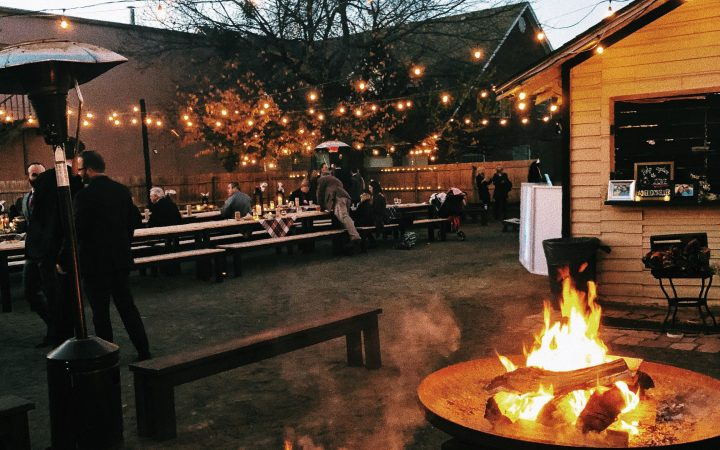 Outdoor patio with fire pits and picnic benches at bar in OKC