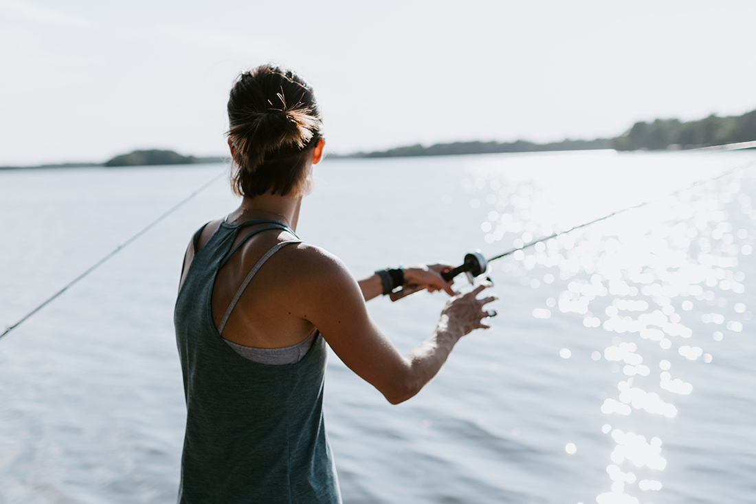 Woman casting a line into a broad lake.