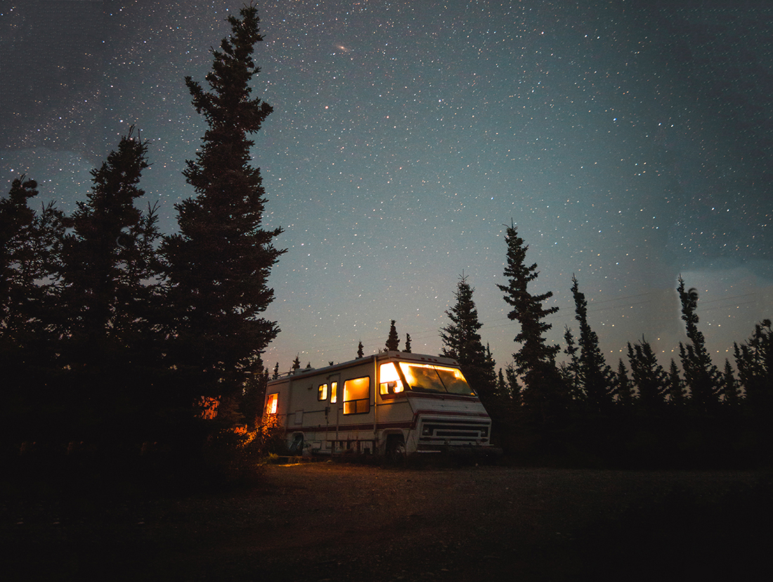 An RV parked under a starry sky in a forest.