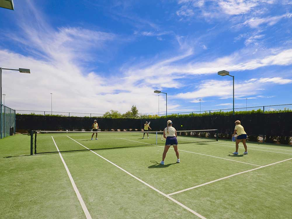 Doubles tennis under blue sky.