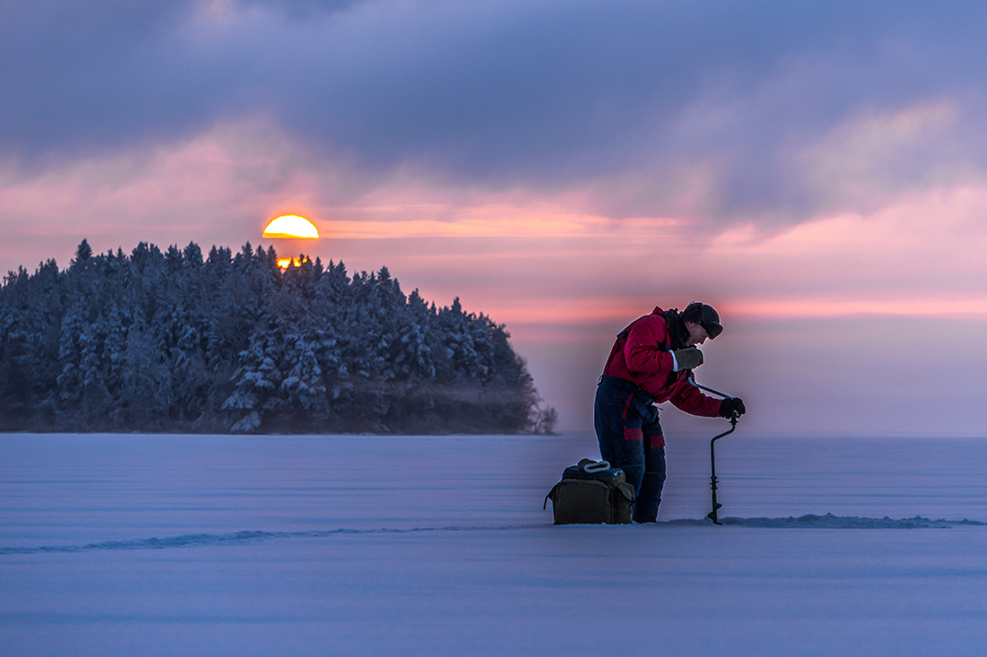 Angler drills through the ice with an auger.