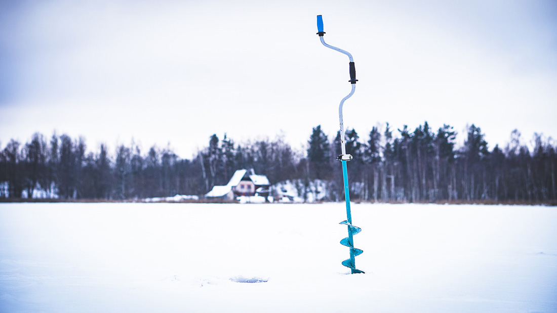 An ice fishing auger stuck into the ice.