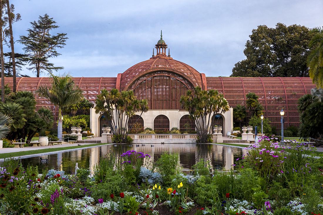 Elegant botanical building reflected on a long lily pond.