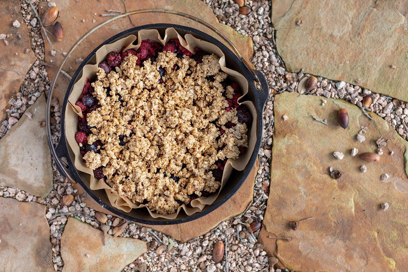 A dutch oven filled with berries and crunched granola