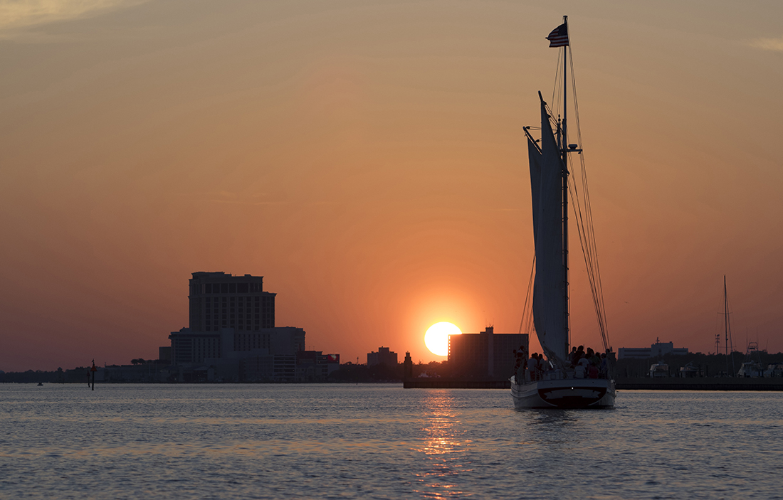 A sailboat glides on the water as the sun sets.