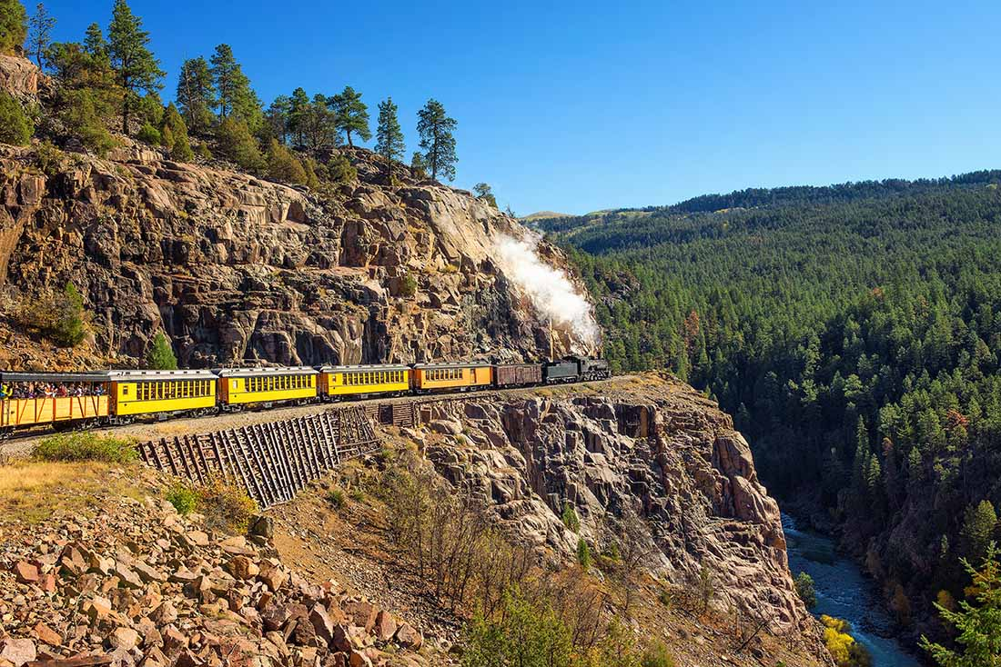 Historic steam engine train travels from Durango to Silverton through the San Juan Mountains in Colorado, USA.
