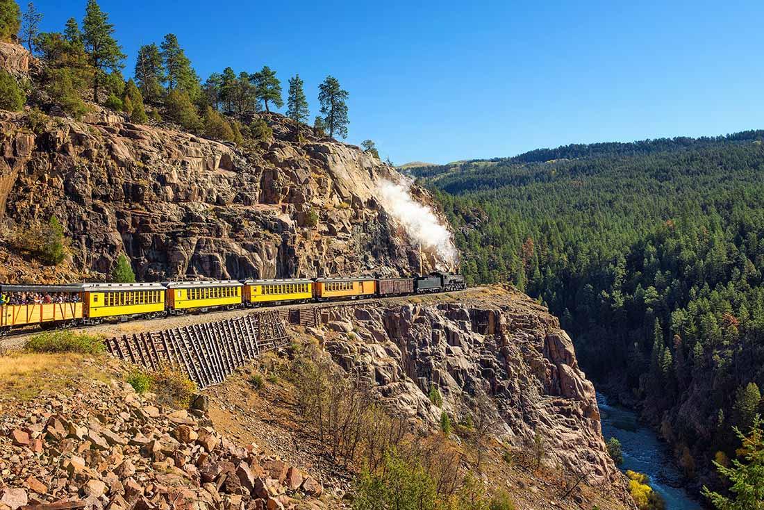 Historic steam engine train travels from Durango to Silverton through the San Juan Mountains in Colorado, USA.