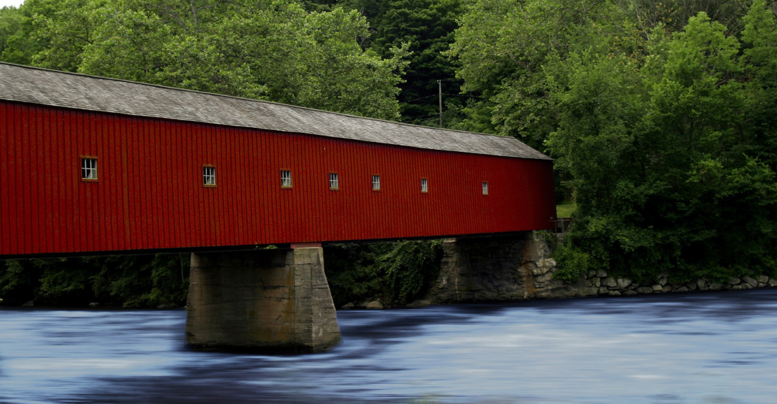 A covered bridge crosses a fast-moving river.
