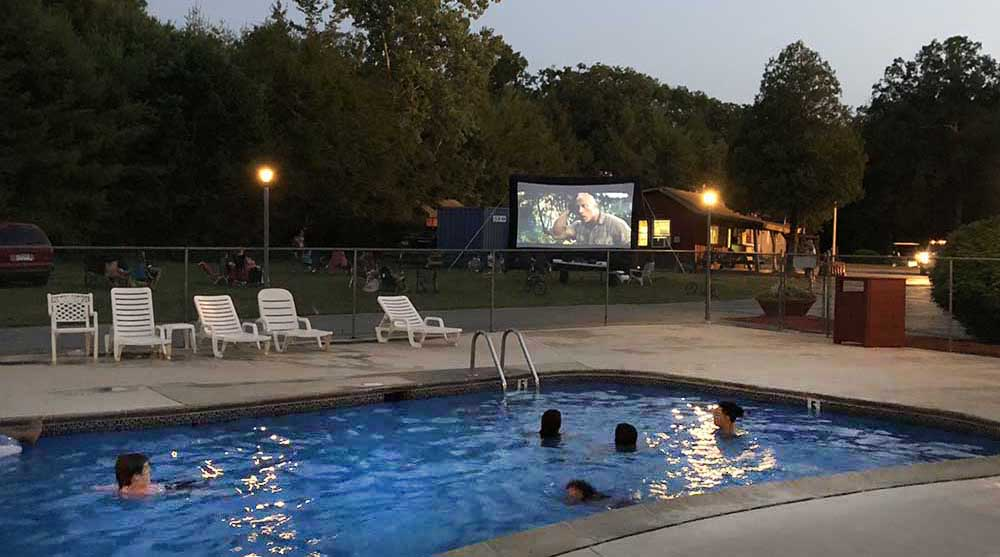 Campground guests watch a movie from a pool.