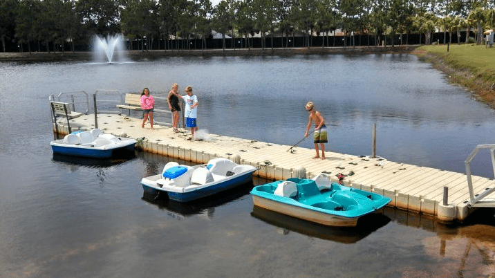 Kids play on a dock with paddleboats.