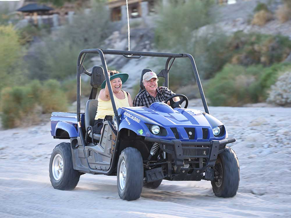 A couple takes a ride in an ATV.
