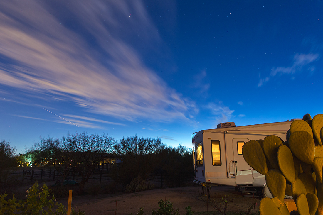 Desert RV camping with cactus in foreground.
