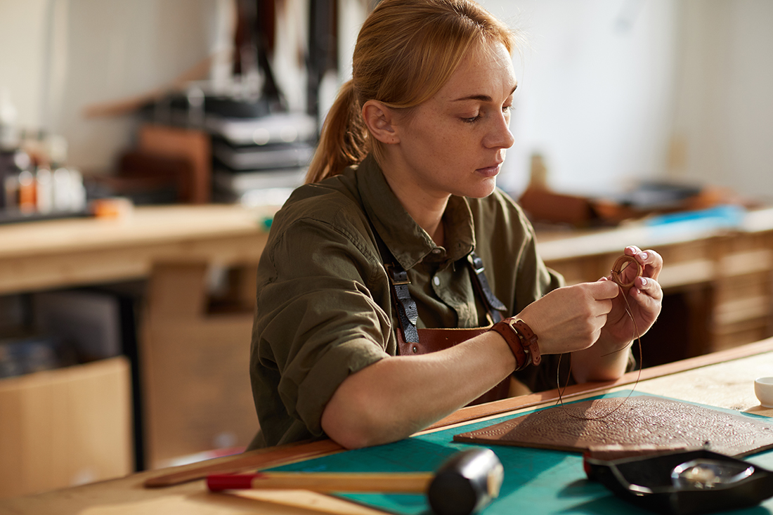 Portrait of woman artisan working with leather while making handcrafted bag in shop lit by sunlight