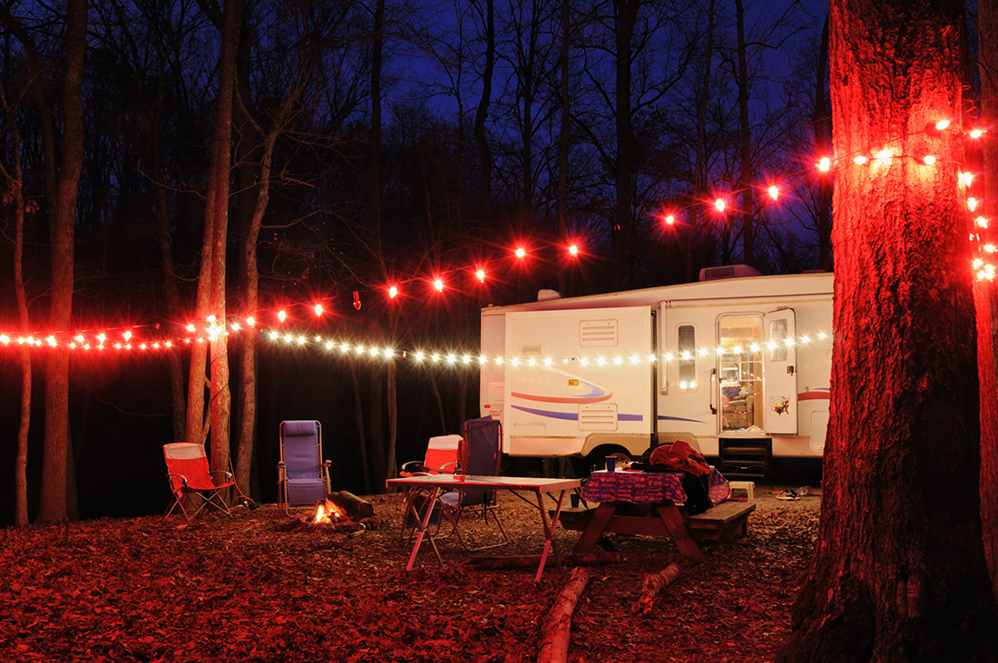 Recreational vehicle travel trailer in campsite at dusk with lights and campfire, horizontal.