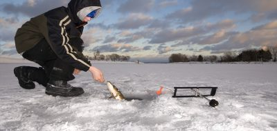 Young boy ice fishing on frozen surface.