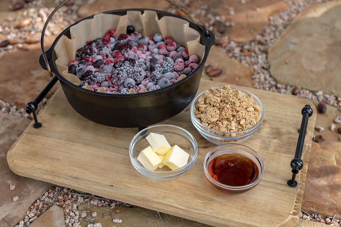 A dutch oven filled with berries surrounded by fixins'.