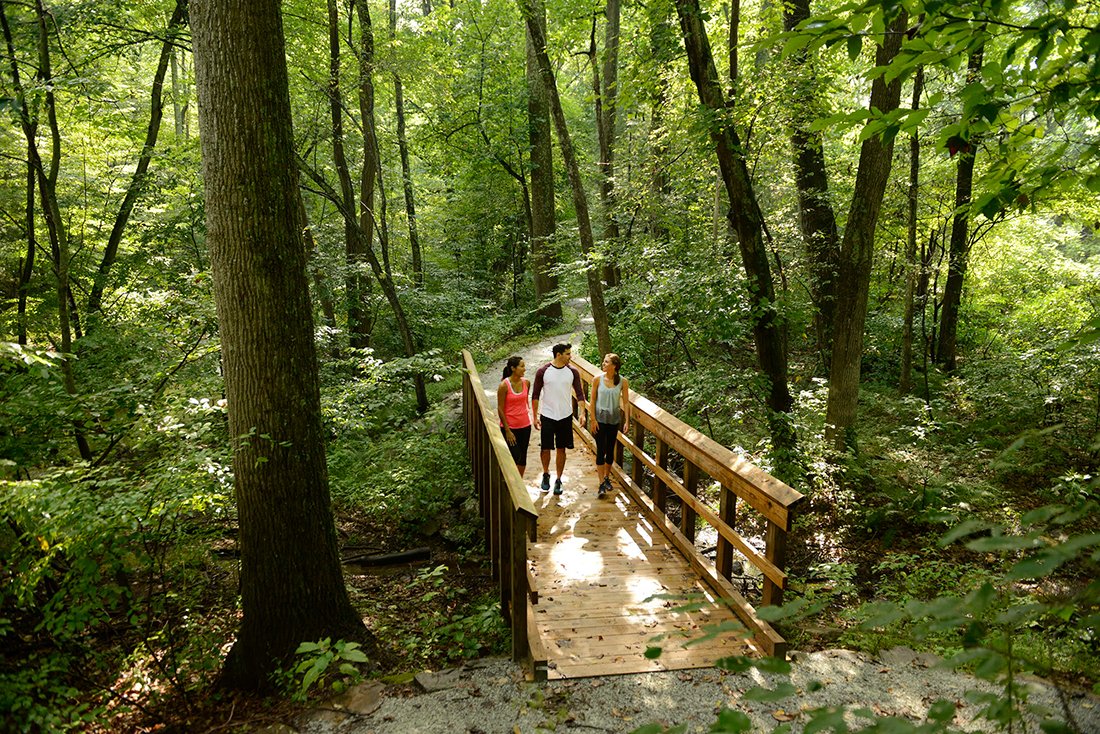 Three people walking over a bridge in a forest, Photo: Visit Pennsylvania Gettysburg, Pennsylvania