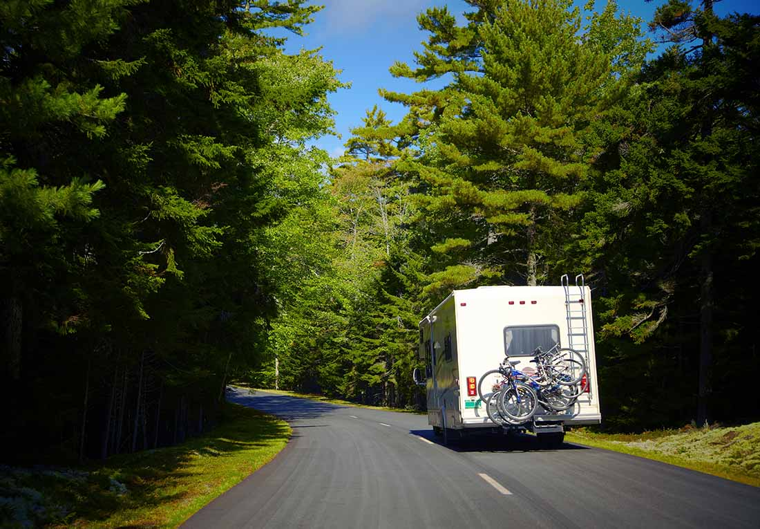 RV driving on a tree-lined road in Maine