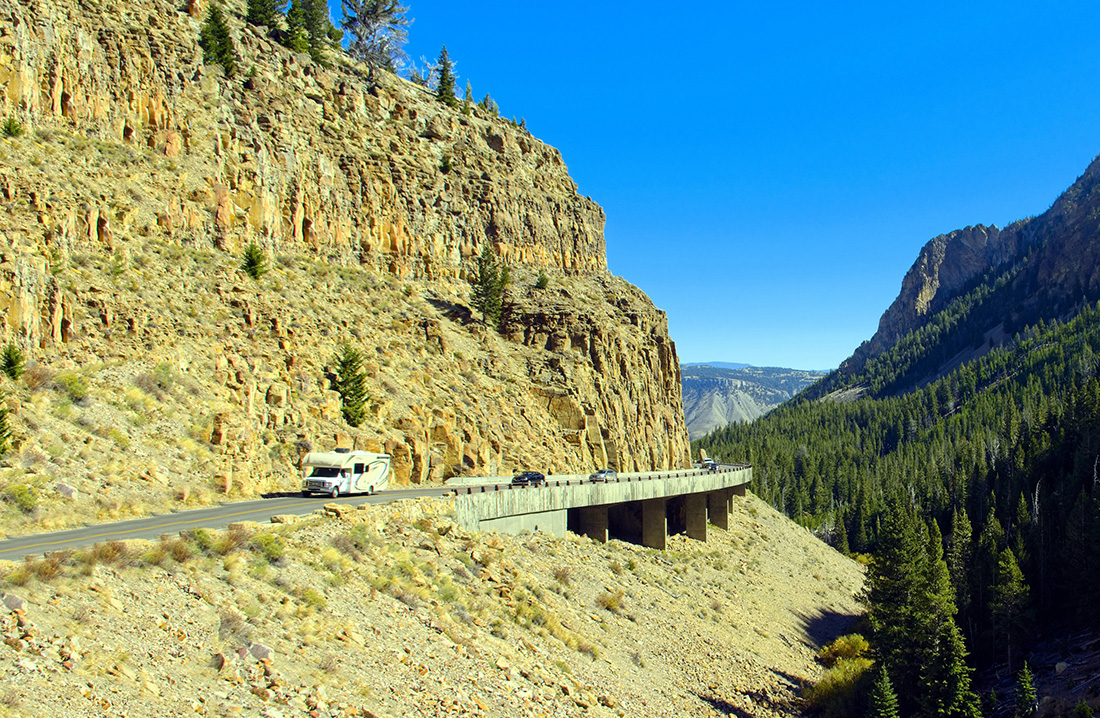 Motorhome driving on Yellowstone mountain road with cliff on one side