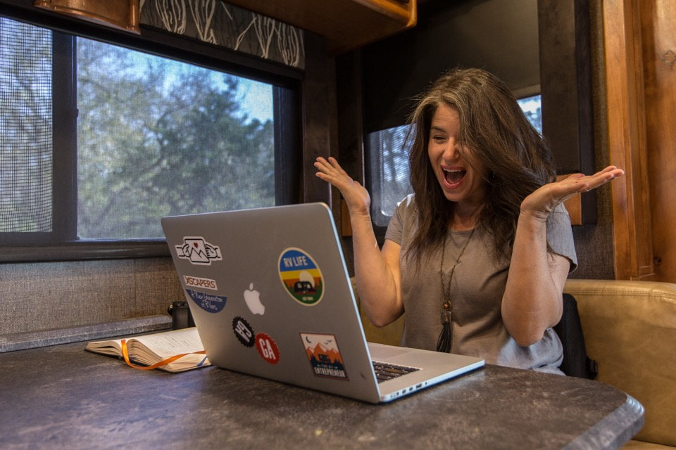 Woman at a table with laptop in RV