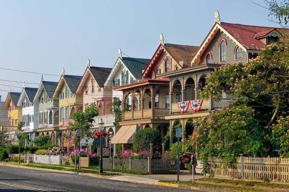 Flag-draped Victorian houses line a residential street.