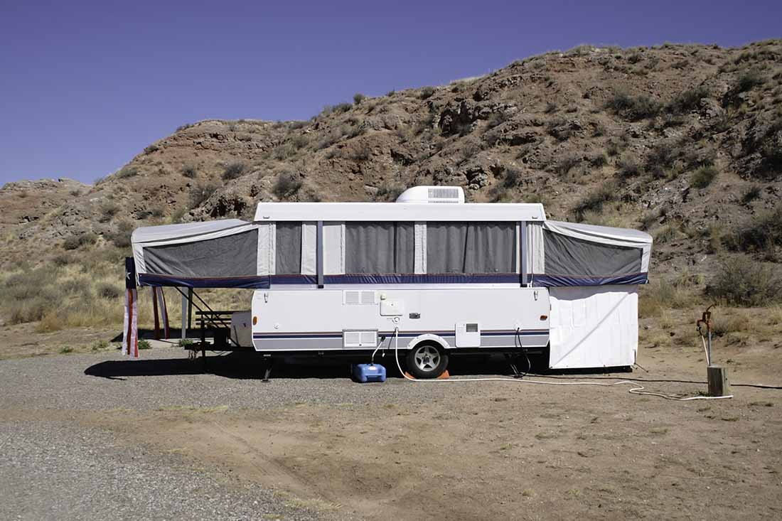 A small camper trailer is parked at a desert campsite in Bottomless Lakes State Park near Roswell, New Mexico.