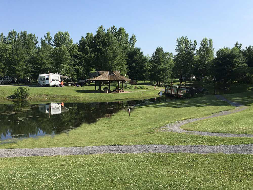 An RV reflected in a pond surrounded by lush treen lawn