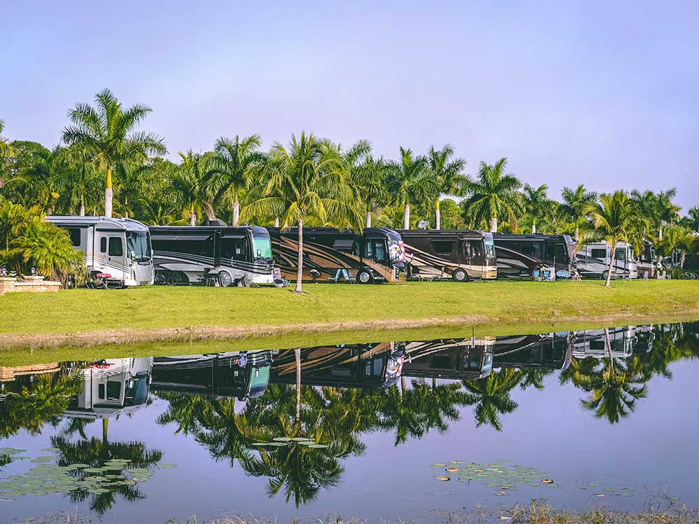 RVs parked in a row reflected on a pond's placid waters.