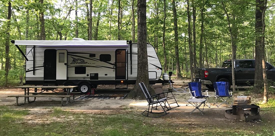RV at campsite under trees