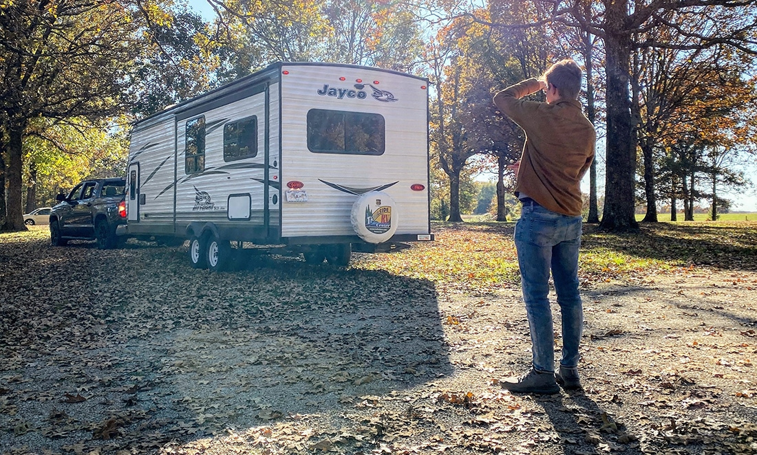 Young man photographs exterior of an RV.