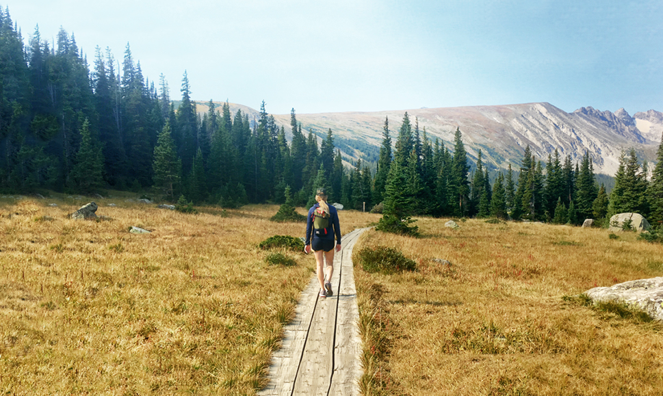 Woman follows a wooden walkway toward mountains.