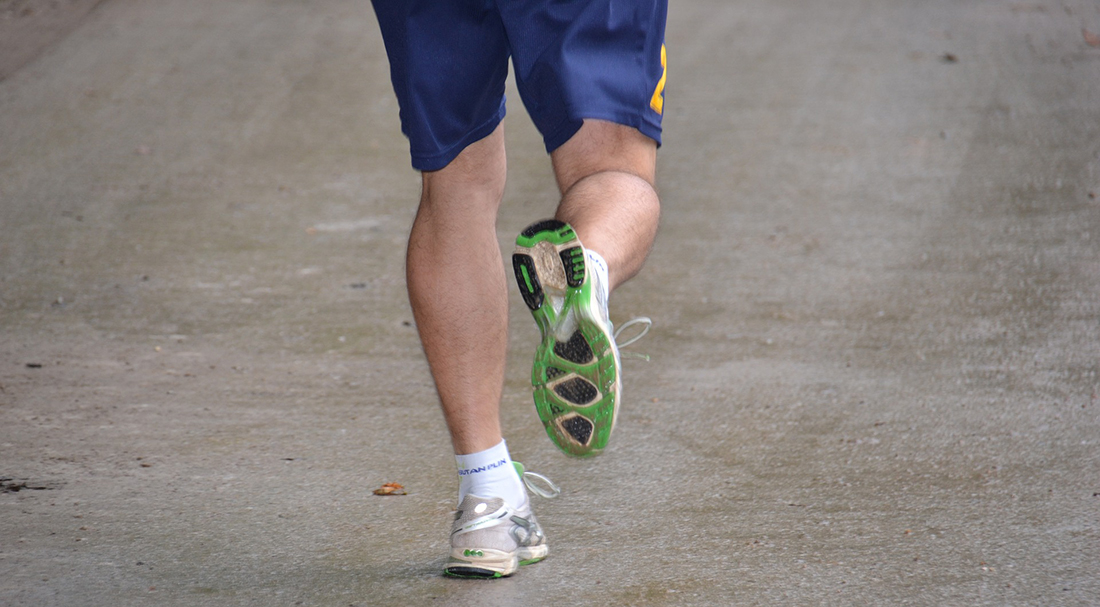 A man running with green-soled shoes.