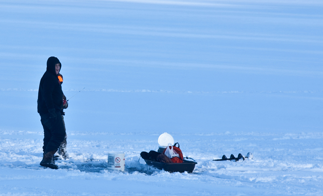 Man on ice with sled and bucket.