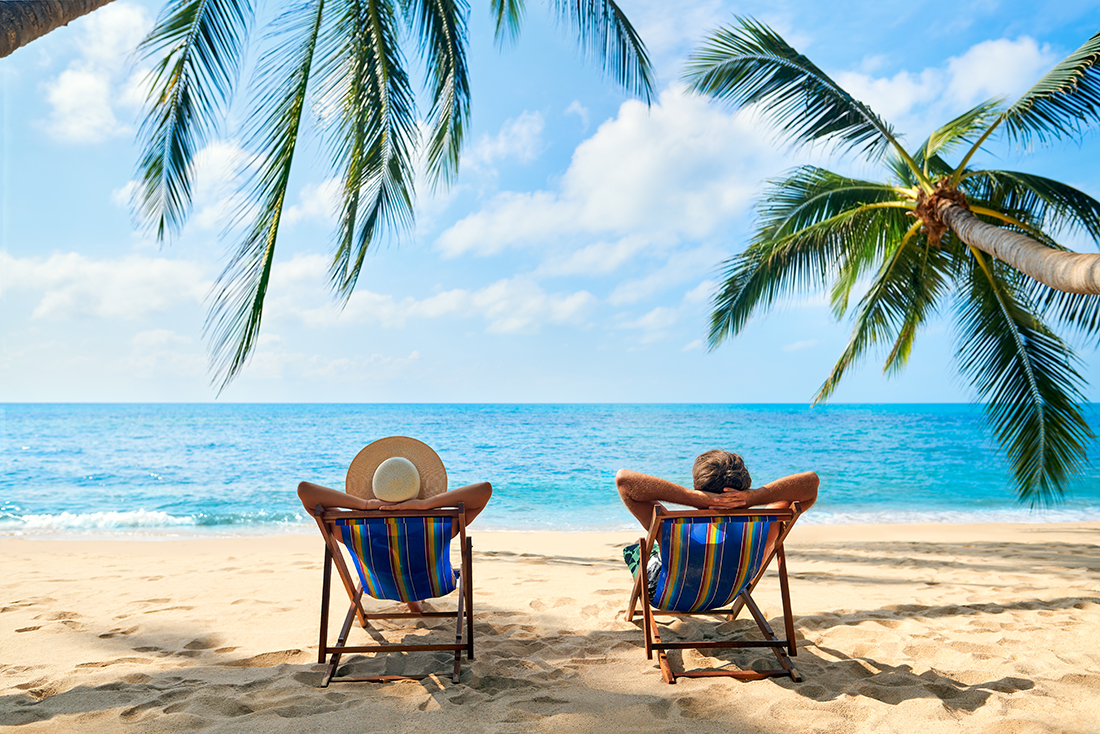 A man and woman lounge in the sand on a tropical beach.