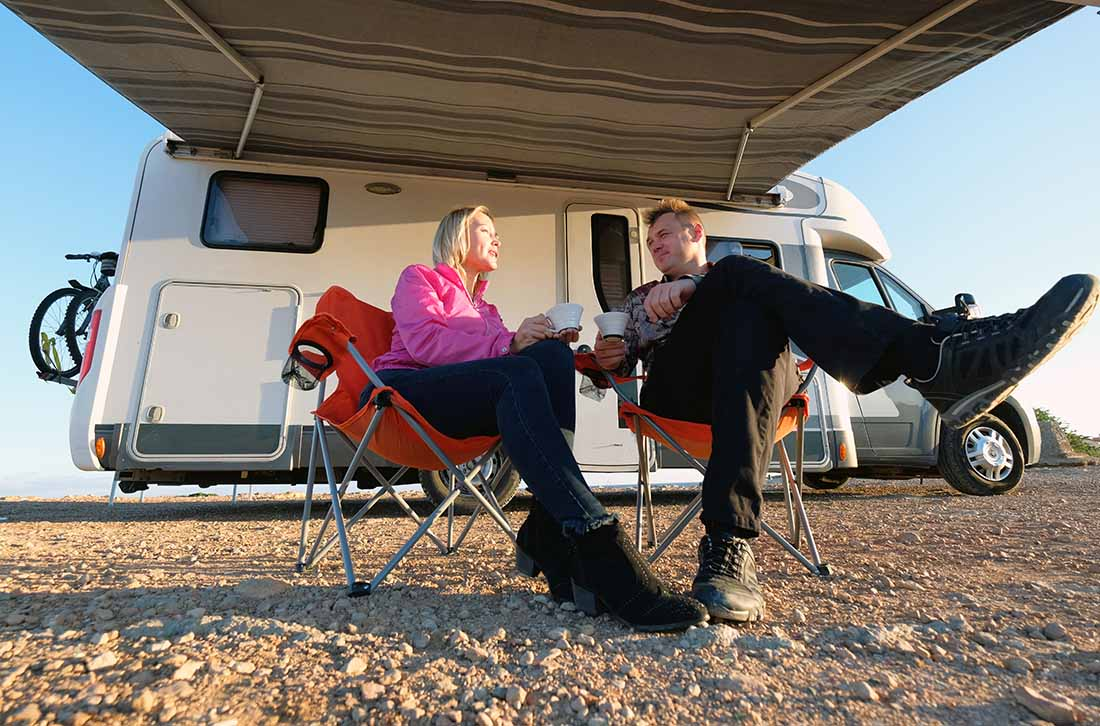Middle aged married couple wife and husband holding cups drinking tea sitting on folding chairs near recreational vehicle motor home trailer take a break during trip resting talking feel happy
