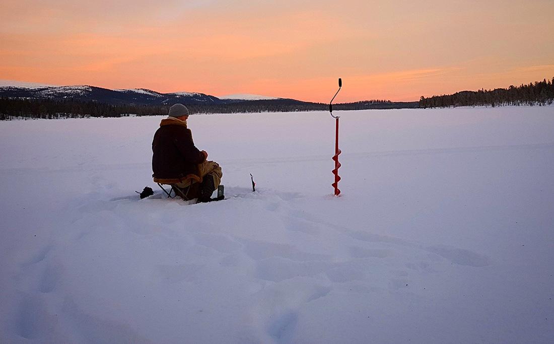 Ice fishing on snowy lake.