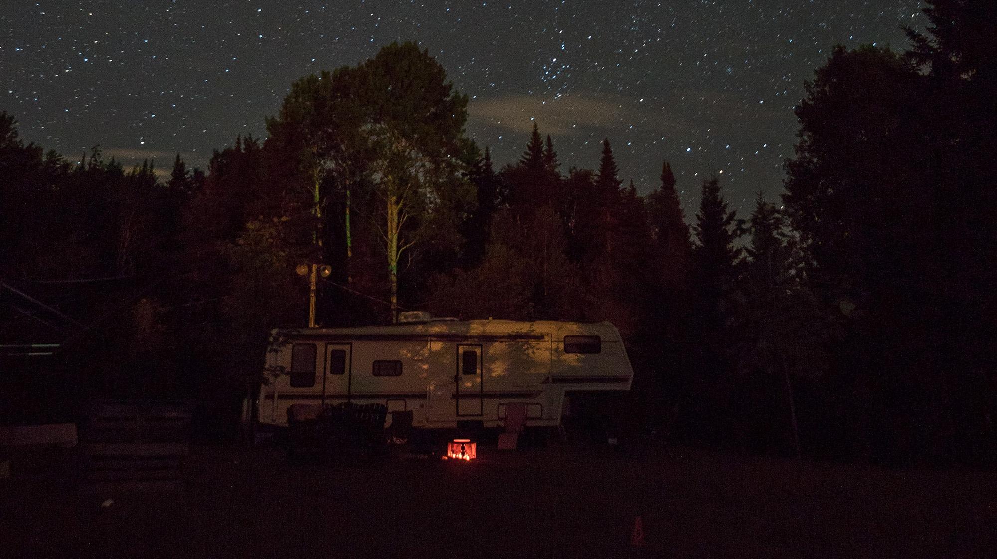 Fifth-wheel trailer under starry sky.