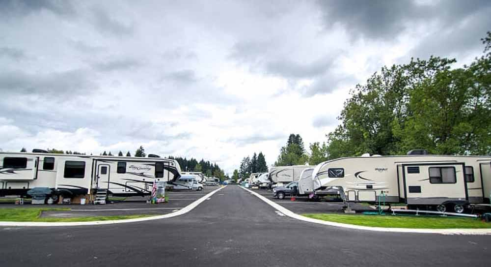 RVs parked along a paved road running through an RV park.