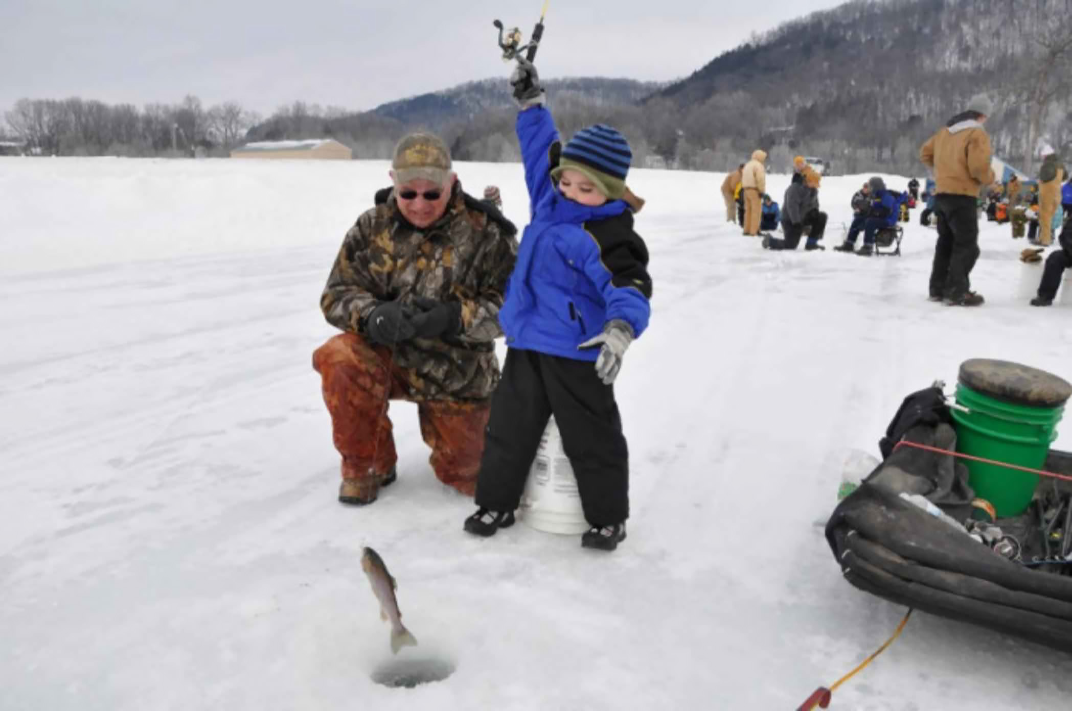 Young boy catches fish on the ice.