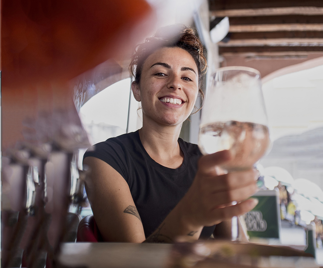 A woman smiles as she raises a wine glass