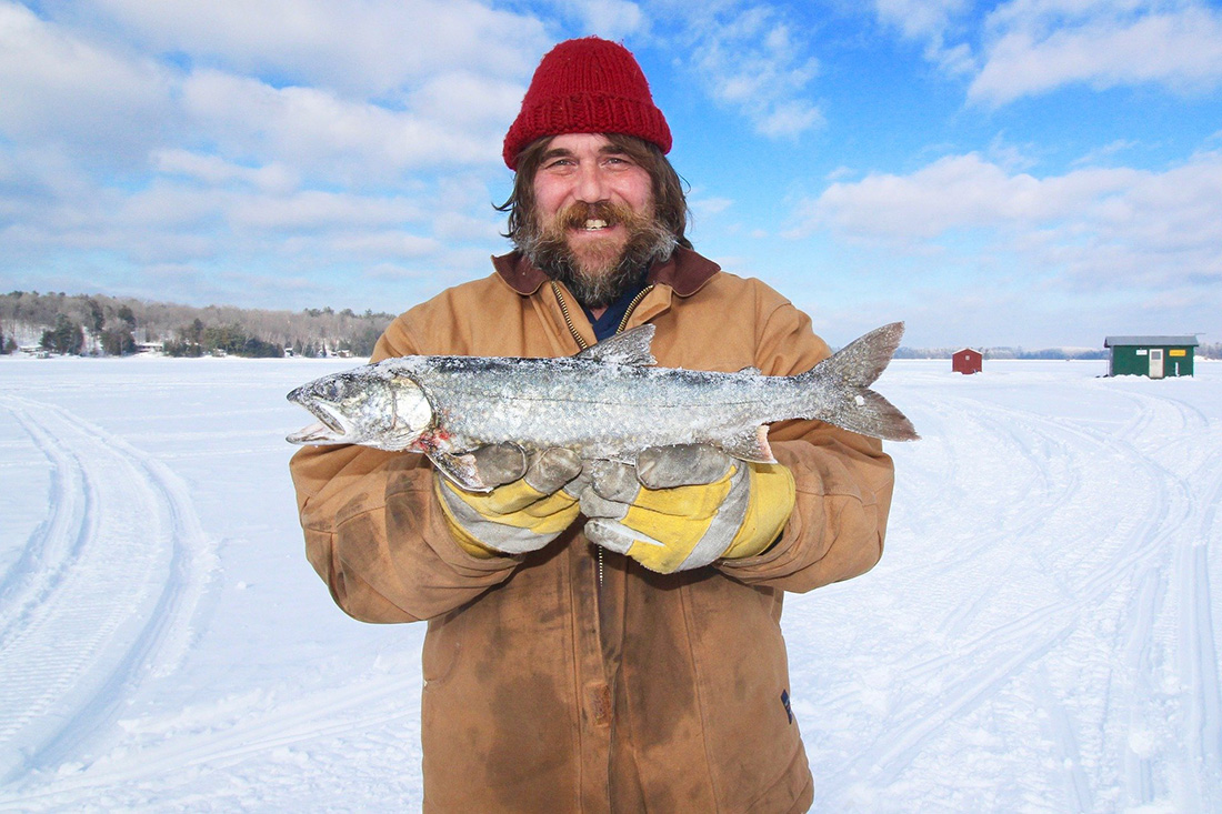 A man holding a fish on a frozen lake.