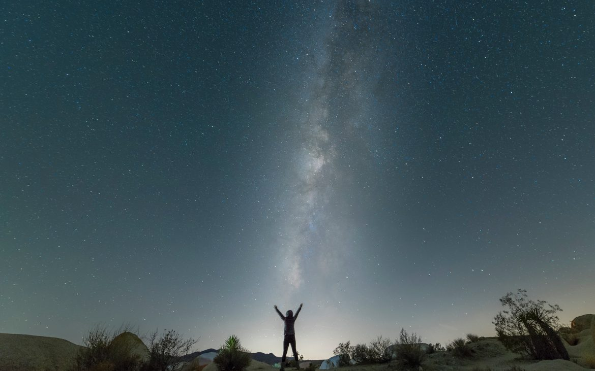 Man standing outstretched arms under star filled night sky at Joshua Tree National Park