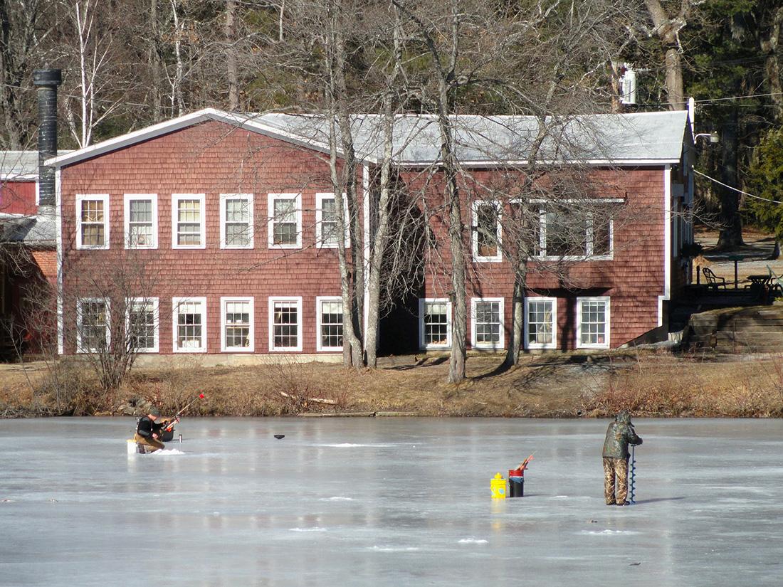 Two men ice fishing on a Massachusetts lake.