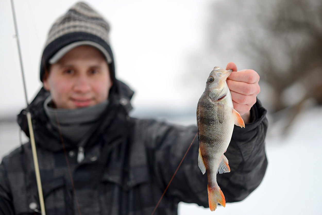 man holding a fish caught in the winter