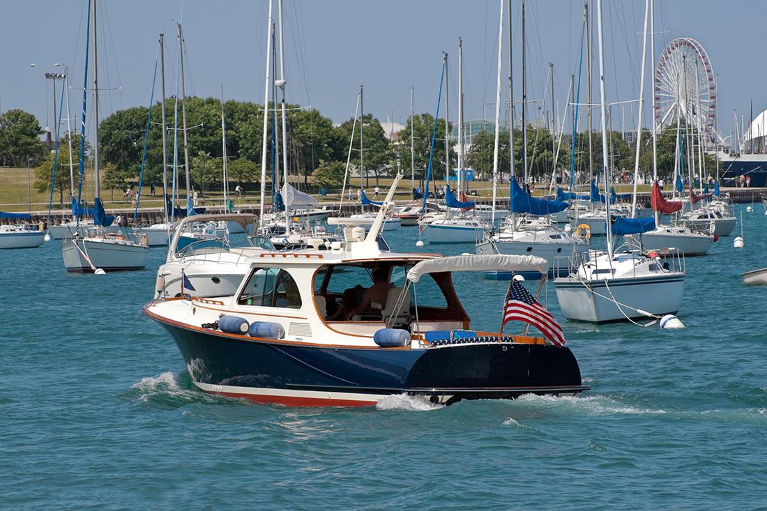 A boat chugs along Chesapeake Bay, flag flying.