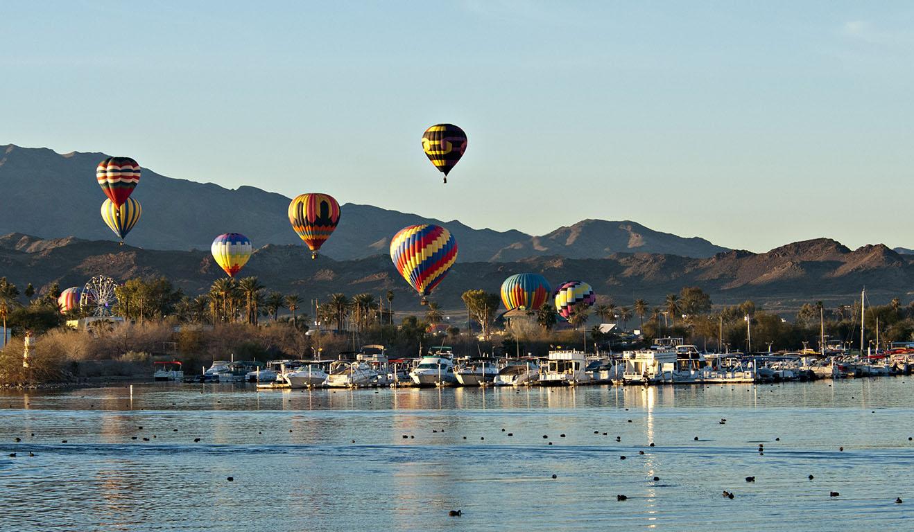 Balloons over a desert lake.