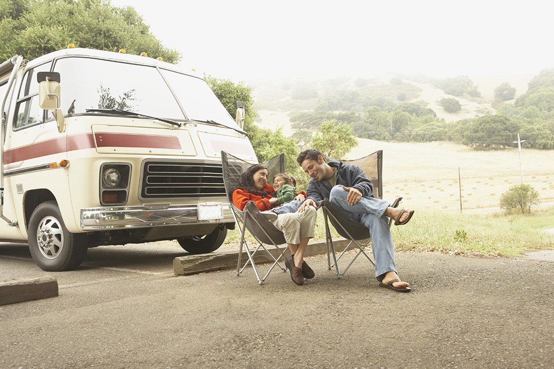 Couple lounging in front of RV with small child.